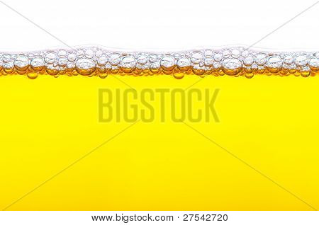 Close Up Shot Of Yellow Beer With Foam And Bubbles On White Background
