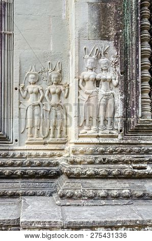 Bas-relief showing devatas, the female divine carved figurines, with crowns, necklaces, armbands, belts and ankle bands adorning the walls of the main complex of Angkor Wat poster