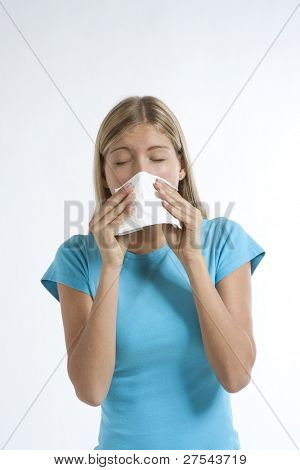 Young woman blowing her nose with kleenex, isolated on white