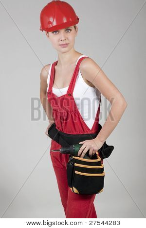 Female handworker with toolbelt, isolated on gray