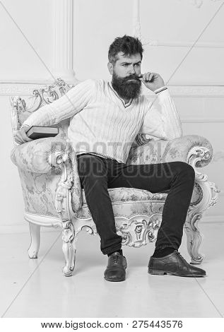 Lecturer Sit On Armchair And Holds Book, White Wall Background. Scientist, Professor On Thoughtful F