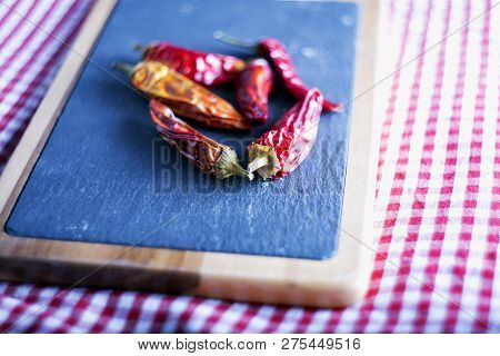 Red Hot Peppers Over Cutboard