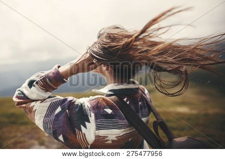 Stylish Hipster Girl With Backpack  And Windy Hair On Top Of Mountains. Portrait Of Happy Young Woma