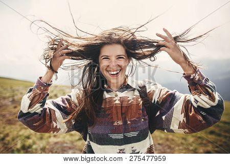 Stylish Hipster Girl With Backpack  And Windy Hair Smiling On Top Of Mountains. Portrait Of Happy Yo