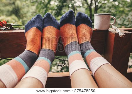 Stylish Socks On Couple Legs And Metal Cup On Wooden Porch With View On Woods In Mountains. Happy Fa