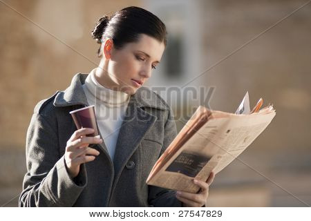Young businesswoman taking a rest with newspaper and coffee