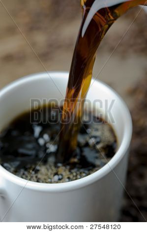 Coffee cup being filled, surrounded by coffee beans
