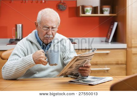 Senior man having coffee and reading newspaper in his kitchen