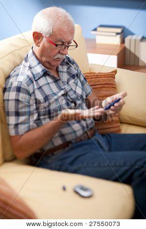 Senior man doing blood sugar test at home