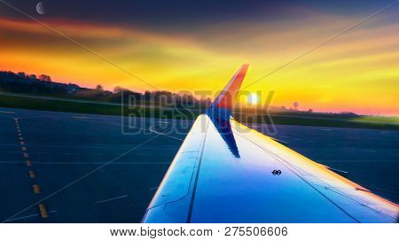 Wing aircraft in altitude during flight . Sunset or sunrise with clouds, light rays and other atmospheric effect . Sunset and new moon poster