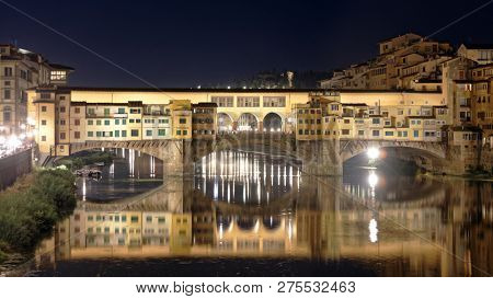 FLORENCE, ITALY - AUGUST 7, 2018: Night view to Ponte Vecchio across Arno river in Florence. The historical center of Florence is listed as UNESCO World Heritage since 1982