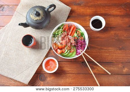 Organic food. Fresh seafood recipe. Tuna poke bowl with crystal noodles, fresh red cabbage, avocado, cherry tomatoes. Food concept poke bowl on wooden background poster