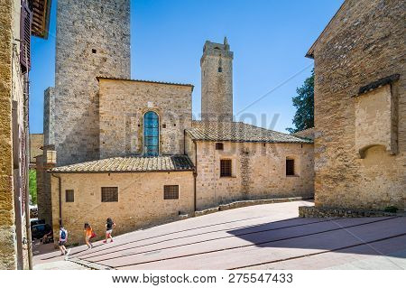 Tourists walking at San Gimignano - mediewal town of towers. Toscana, Italy. poster