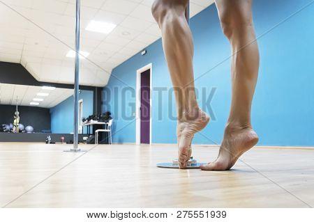 Close Up Of Bare Brawny Legs Of A Poledancer Posing Before Poledance At Dance Hall Background. Girls