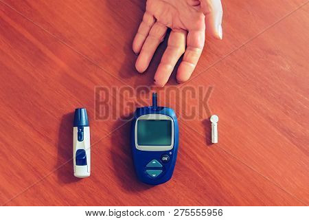 A Ladys Hands Measuring Blood Sugar, Glucose With A Home Test To Control Her Diabetes. Blood Glucose