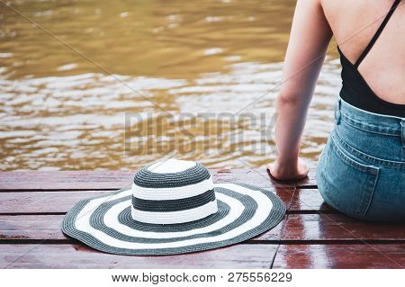 Women Sitting On The Wooden Pier With Her Big Vintage Hat Close Up.
