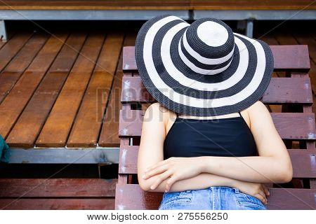 Women Laying Her Body On Wooden Bed And Using A Big Vintage Hat Masked Her Face.