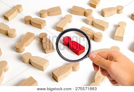 Magnifying Glass Is Looking At The Red Human Figure Among Many Other People. Employee Search Concept