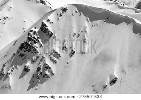 Snow cornice in winter mountains in cold sunny day. Caucasus Mountains, region Dombay. View from top of Mount Musa Achitara. Black and white toned landscape. poster
