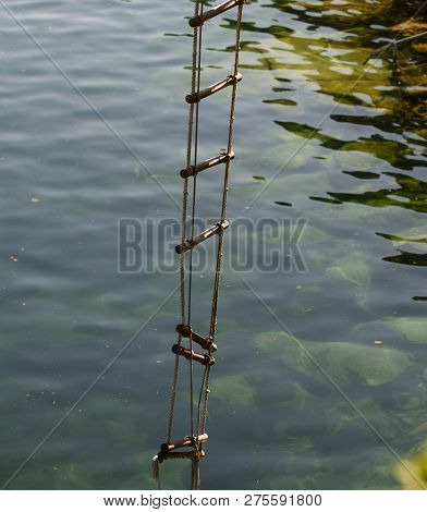 The Ladder Of Success Is Never Crowded At The Top. Rope Ladder With Wooden Steps. Rope Over Water Su