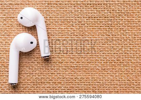 White Wireless Headphones On A Beautiful Wicker Napkin