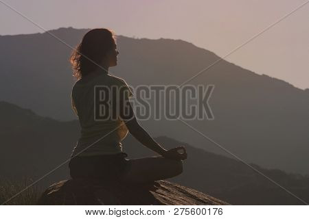Woman Sitting On The Rock And Meditating In Yoga Pose. Back View Silhouette Of Meditating Woman