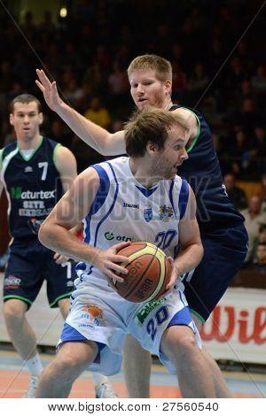 KAPOSVAR, HUNGARY - DECEMBER 10: Joshua Wilson (in white) in action at a Hungarian Championship basketball game Kaposvar (white) vs. Szeged (blue) on December 10, 2011 in Kaposvar, Hungary.