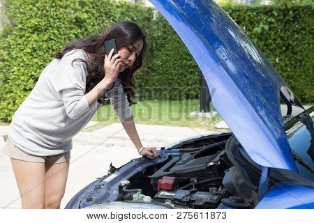 Young Asian Woman Using Mobile Phone Call A Car Mechanic While Looking At Broken Down Car On Street,