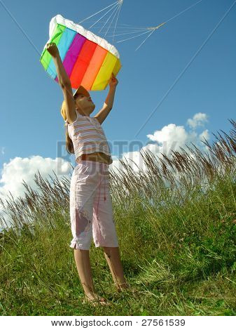 child starts flying kite against blue sky with clouds