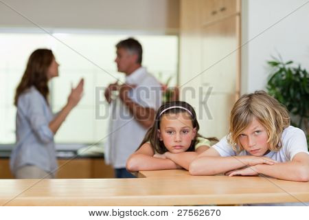 Sad looking siblings with their arguing parents behind them