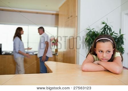 Sad girl listening to her fighting parents