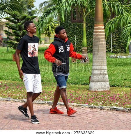 African Boys Chatting And Walking Along A Road In A Resort With Green Trees In The Background. Trave