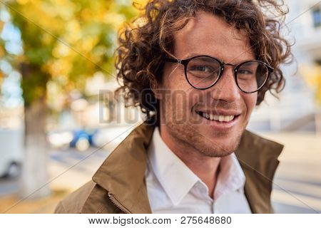 Closeup Horizontal Portrait Of Young Happy Business Man With Glasses Smiling And Posing Outdoors. Ma