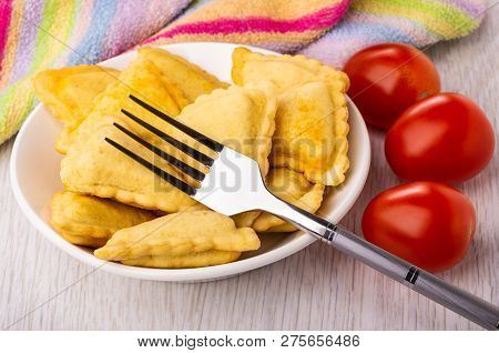 Small Fried Savory Pies In White Plate, Fork, Striped Napkin, Red Tomatoes On Wooden Table