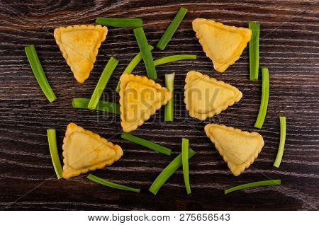 Small Fried Savory Pies And Pieces Of Green Onion On Wooden Table. Top View