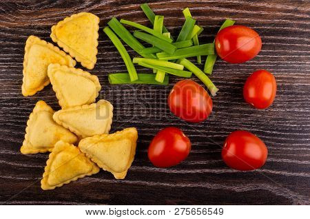 Small Fried Savory Pies, Pieces Of Green Onion, Red Tomatoes On Wooden Table. Top View