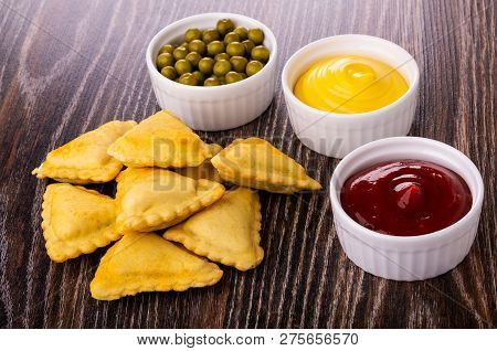 Small Fried Savory Pies, Glass Bowls With Ketchup, Mayonnaise And Green Peas On Wooden Table