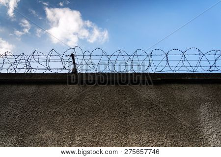 Barbed Wire Fence Around Prison Walls, Blue Cloudy Sky In Background, Security, Crime Or Illegal Imm