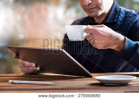 Man Working On Tablet And Having His Coffee In Office Room