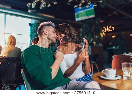 Happy Mixed Race Couple Having Fun At The Coffee Shop. Couple Enjoying At A Coffee Shop, Sitting At