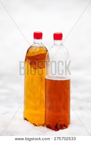 Two Plastic Beer One Litre Bottles Full And Half With Red Caps O