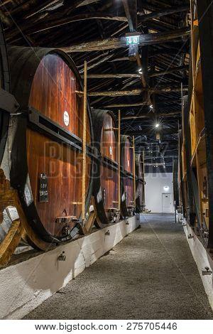 Porto, Portugal - January 16, 2018: Row of wooden porto wine barrels in wine cellar Porto, Portugal.