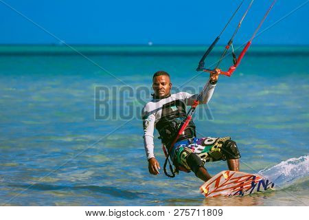 Egypt, Hurghada - 30 November, 2017: Close-up surfer with kite equipment standing on the surfboard. The Red sea shore. Unidentified Arab man surfing on the water surface. Extreme sport outdoor