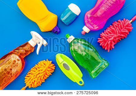 Housecleaning With Detergents, Soap, Cleaners And Brush In Plastic Bottles On Blue Background Top Vi