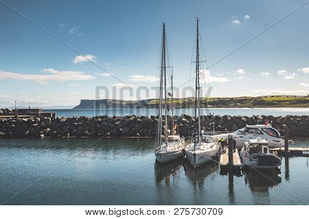 Touristic yachts, boat next to the small pier and stone fence. Northern Ireland. Comfortable vehicles in the bay. Irish green covered hills background. Ideal place for the rest and relax.