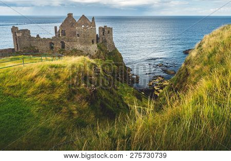 Dunluce castle on the green covered cliff. Irish shoreline. Overwhelming Northern Ireland landscape. Ancient now-ruined Medieval building with the ocean view. Famous archeological and touristic site.