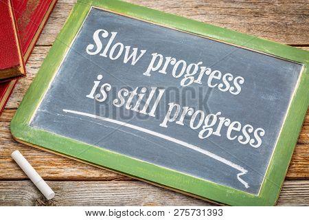 Slow progress is still progress - inspirational writing on a slate blackboard