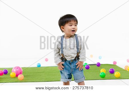 Studio Portrait Of Adorable Toddler Boy Wearing Denim Overalls, Long Sleeve T-shirt, Smiling, Hands