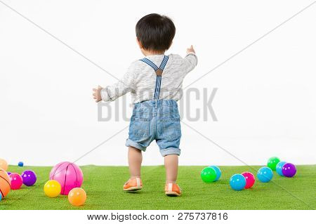 Studio Portrait Of Backside Of Adorable, Asian Toddler Boy Wearing Denim Overalls, Long Sleeve T-shi