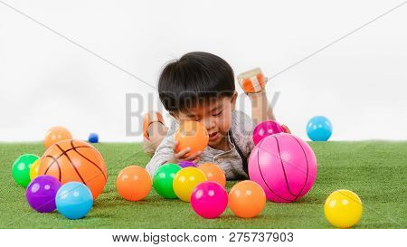 Studio Portrait Of Adorable, Asian Toddler Boy Wearing Denim Overalls, Long Sleeve T-shirt, Lying On